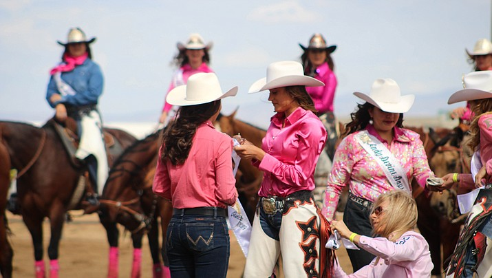Adison getting her crown and chaps being passed down by the previous queen, Dalace Beiswenger, and her mother, Tiffany Leo, helping her put on the chaps. (Photo by Vanessa Espinoza/Daily Miner)