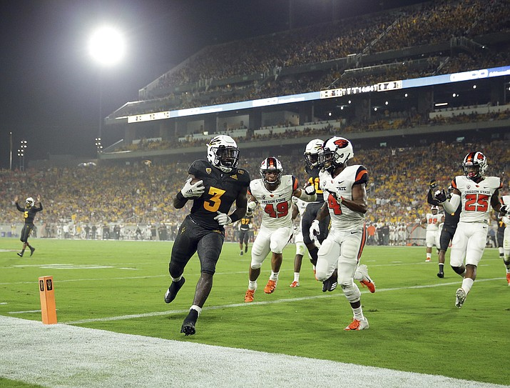 Arizona State running back Eno Benjamin (3) scores a touchdown as Oregon State cornerback Dwayne Williams (4) and linebacker Andrzej Hughes-Murray (49) defend during the first half of an NCAA college football game Saturday, Sept. 29, 2018, in Tempe. (Matt York/AP)