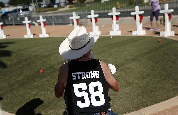 "Jim Strickland, of Oroville, Calif., writes a message on a cross at a makeshift memorial for victims of the Oct. 1, 2017, mass shooting in Las Vegas, Sunday, Sept. 30, 2018, in Las Vegas. ""I needed some closure so I had to come back,"" said Strickland, who was at the music festival and came back for the anniversary. (John Locher/AP)"