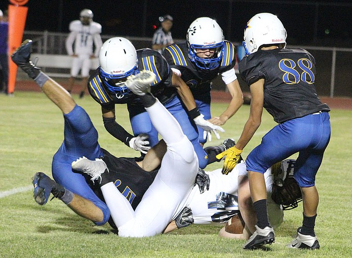 A pack of Bulldogs bring down a ball carrier earlier this season against Paradise Honors. Kingman hits the road for a 7 p.m. contest Friday at Chino Valley. (Daily Miner file photo)