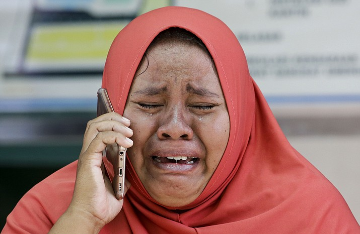A woman cries as she uses the recovered mobile phone of her daughter who was killed in the massive earthquake at Palu, Central Sulawesi, Indonesia Thursday, Oct. 4, 2018. The mother did not get the chance to see the body of her daughter after she was buried earlier in a mass grave. Life is on hold for thousands living in tents and shelters in the Indonesian city hit by a powerful earthquake and tsunami, unsure when they'll be able to rebuild and spending hours each day often futilely trying to secure necessities such as fuel for generators. (AP Photo/Aaron Favila)