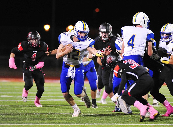 Prescott's Austin Clark stiff arms a tackler as the Badgers defeated crosstown rival Bradshaw Mountain Friday night 26-21 in Prescott Valley. (Les Stukenberg/Courier)