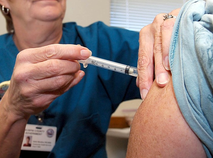 An registered nurse with Yavapai County Community Health Services administers a flu shot to a client. (Courier, file photo)