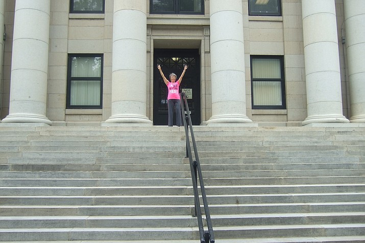 "Deborah Portzer, ""Rocky"" style triumphant at the top of the Yavapai County Courthouse stairs. (Nanci Hutson/Courier)"