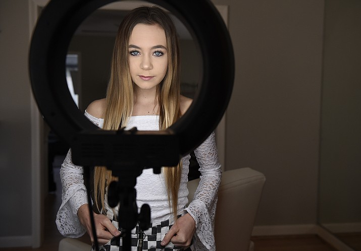 Matty Nev Luby poses for a photograph in front of a ring light she uses for her internet posts in Wethersfield, Conn. Teens and young adults say cyberbullying is a serious problem for people their age, but most don't think they'll be the ones targeted for digital abuse. (Jessica Hill/AP)