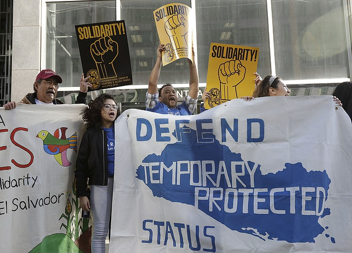 "FILE - In this Monday, March 12, 2018, file photo, supporters of temporary protected status immigrants hold signs and cheer at a rally before a news conference announcing a lawsuit against the Trump administration over its decision to end a program that lets immigrants live and work legally in the United States outside of a federal courthouse in San Francisco. A judge on Wednesday, Oct. 3, 2018, blocked the Trump administration from ending protections that let immigrants from four countries live and work legally in the United States, saying the move would cause ""irreparable harm and great hardship."" (AP Photo/Jeff Chiu, File)"