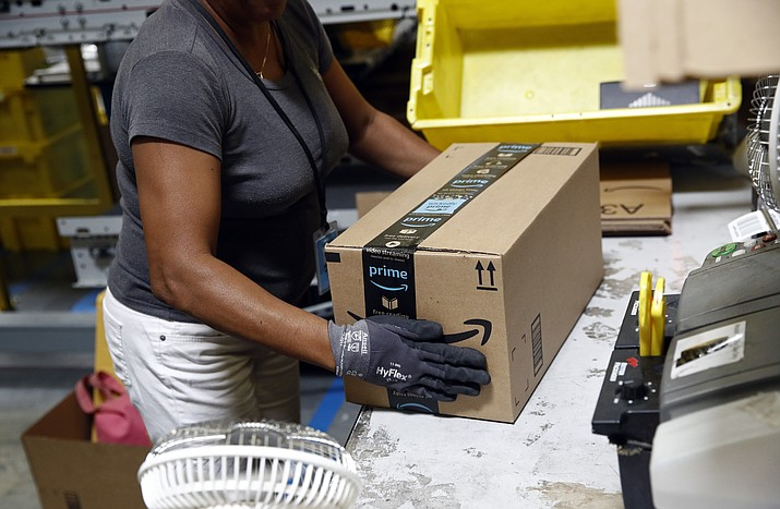 In this Aug. 3, 2017, file photo, Myrtice Harris applies tape to a package before shipment at an Amazon fulfillment center in Baltimore. Amazon's announced Tuesday, Oct. 2, 2018, that it would raise its hourly minimum wage to $15. Those who already made $15 will get an extra dollar an hour when the change is made next month, but they will also lose two benefits they relied on: monthly bonuses that could top hundreds of dollars and a chance to own Amazon's sky-rocketing stock, currently worth nearly $2,000. (Patrick Semansky/AP, File)