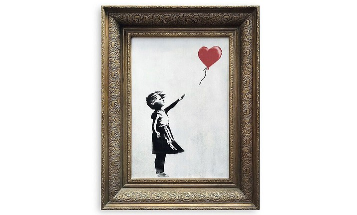 In this undated photo provided by Sotheby's the spray-painted canvas 'Girl with Balloon' by artist Banksy is pictured. Art prankster Banksy has struck again. A work by the elusive street artist self-destructed in front of startled auction-goers on Friday, Oct. 5, 2018 moments after being sold for 1.04 million pounds ($1.4 million). In an Instagram post Saturday, Banksy claimed the dramatic artistic payoff had been years in the making. (Sotheby's/via AP)