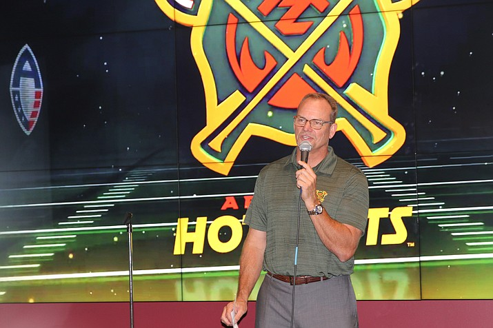 Scott Brubaker, president of the Arizona Hotshots, stands in front of his team's logo. (Photo by Ricardo Ávila/Cronkite News)
