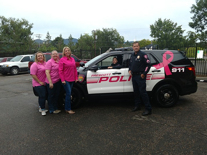 Civilian employees, from left, Denise Buchanan, Junette Ellis and Joyce Anderson. Deputy Chief Amy Bonney is seated in the car and Lead Officer David Fuller, standing next to the police vehicle showcasing the Breast Cancer Awareness theme, which is courtesy of Auto Trim, located in Prescott. (Prescott Police Department/Courtesy)