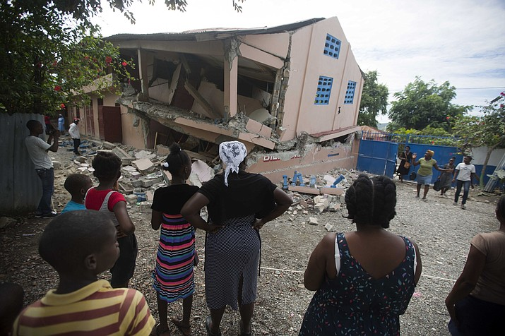 Residents stand looking at a collapsed school damaged by a magnitude 5.9 earthquake the night before, in Gros Morne, Haiti, Sunday, Oct. 7, 2018. Emergency teams worked to provide relief in Haiti on Sunday after the quake killed at least 11 people and left dozens injured. (Dieu Nalio Chery/AP)