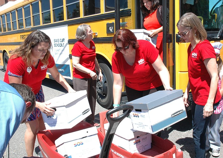 Volunteers from the Save Our Schools movement unload petitions last year to block a voucher-expansion plan approved by state lawmakers from taking effect until voters get the final say in November. (Howard Fischer/Capitol Media Services)
