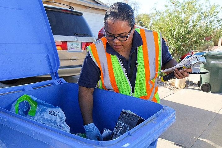 Monica Strauss of the Phoenix Public Works Department digs through a blue bin to see how much of the contents can actually be recycled, part of a city effort to keep contaminants from spoiling entire truckloads of recyclables. (Photo by Stephanie Morse/Cronkite News)