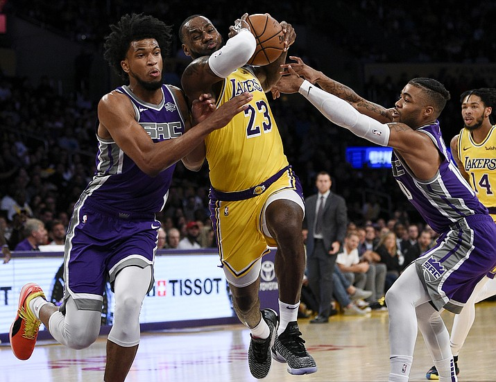 Los Angeles Lakers forward LeBron James, center, drives the ball between Sacramento Kings forward Marvin Bagley III, left, and guard Frank Mason III during the first half of an NBA preseason basketball game in Los Angeles, Thursday, Oct. 4, 2018. (Kelvin Kuo/AP)