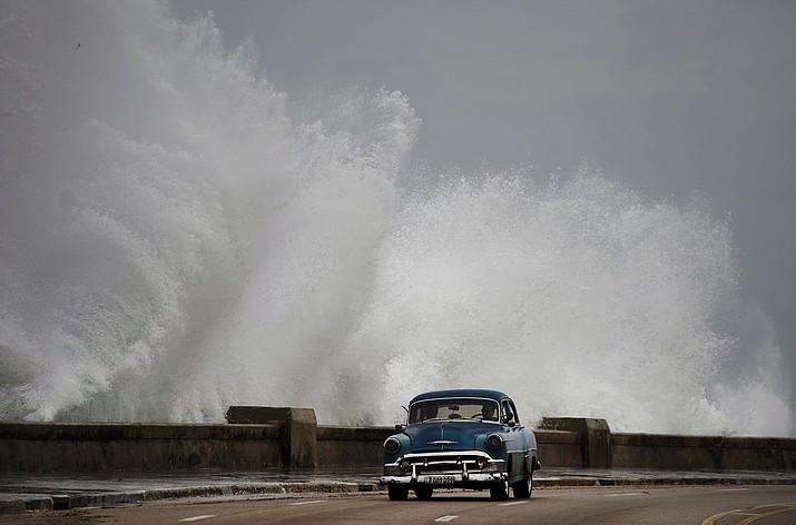 Waves crash against the Malecon, triggered by the outer bands of Hurricane Michael, as man drives past in a classic American car in Havana, Cuba, Tuesday, Oct. 9, 2018. A fast and furious Hurricane Michael is churning toward the Florida Panhandle with 110 mph winds and a potential storm surge of 12 feet, giving tens of thousands of people precious little time to get out. (Ramon Espinosa/AP)