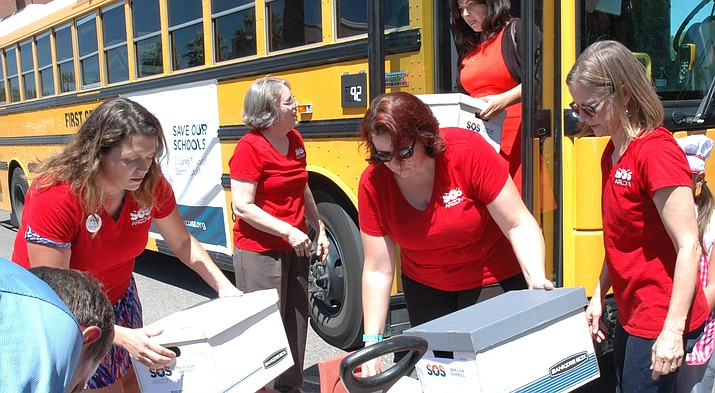 Volunteers from the Save Our Schools movement unload petitions last year to block a voucher-expansion plan approved by state lawmakers from taking effect until voters get the final say in November. (Capitol Media Services file photo by Howard Fischer)