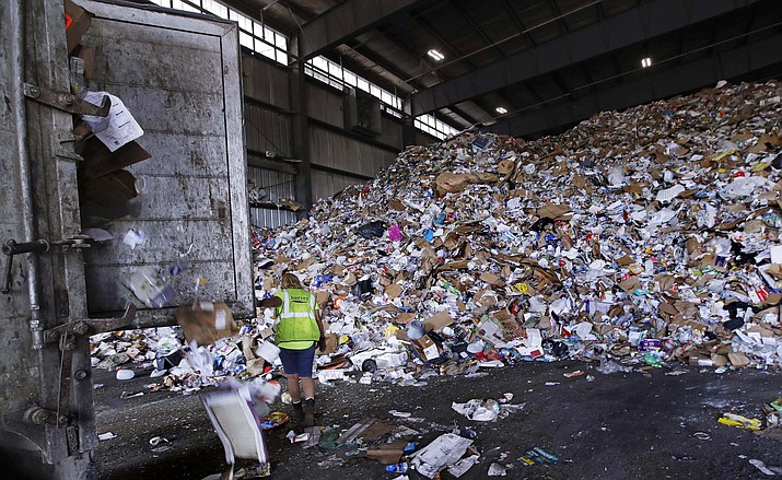In this Thursday, Sept. 6, 2018, photo, a trailer door is opened on a truck filled with unsorted recyclable refuse as it is offloaded and added to a giant pile in a processing building at EL Harvey & Sons, a waste and recycling company, in Westborough, Mass. Recycling programs across the United States are shutting down or scaling back because of a global market crisis blamed on contamination at the curbside bin. (Charles Krupa/AP)