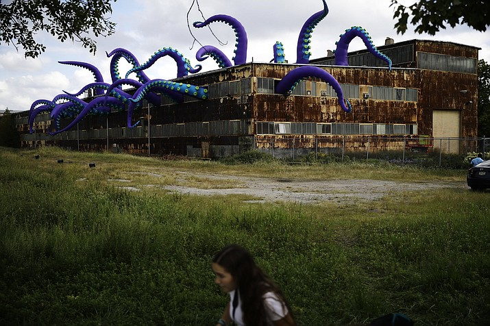 "An inflatable sculpture entitled ""Sea Monsters HERE"" extends from a rusting warehouse called Building 61 at the Navy Yard in Philadelphia, Tuesday, Oct. 9, 2018. The installation was created by UK-based artists Filthy Luker and Pedro Estrellas. The former military base is free and open to the public. (AP Photo/Matt Rourke)"