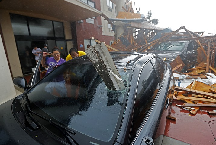 A woman checks on her vehicle as Hurricane Michael passes through, after the hotel canopy had just collapsed, in Panama City Beach, Fla., Wednesday, Oct. 10, 2018. (Gerald Herbert/AP)