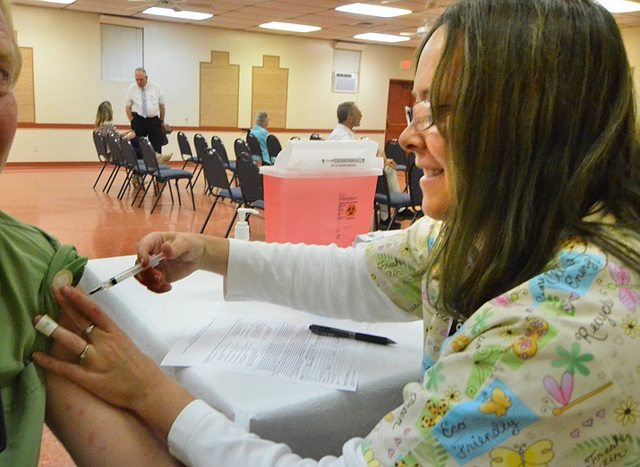 Yavapai County nurse Christine Dixon gives a flu shot in the Verde Village Clubhouse Wednesday. VVN/Vyto Starinskas