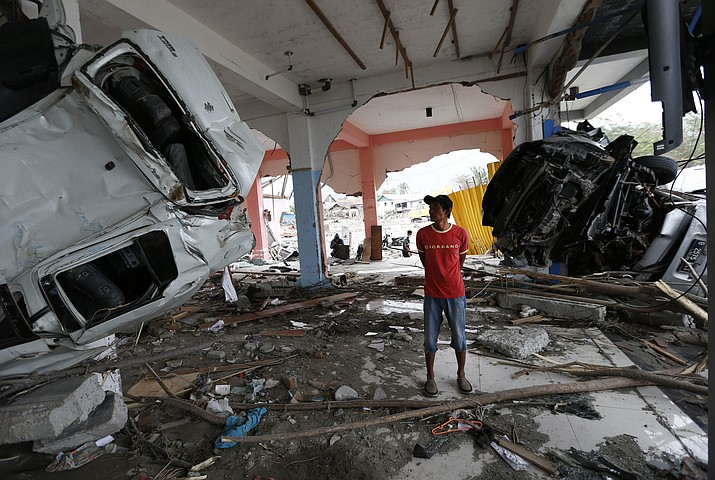 A man inspects the wreckage of vehicles inside a building at the tsunami-ravaged area in Palu, Central Sulawesi, Indonesia, Thursday, Oct. 11, 2018. A 7.5 magnitude earthquake rocked Central Sulawesi province on Sept. 28, triggering a tsunami and mudslides that killed a large number of people and displaced tens of thousands of others. (Dita Alangkara/AP)