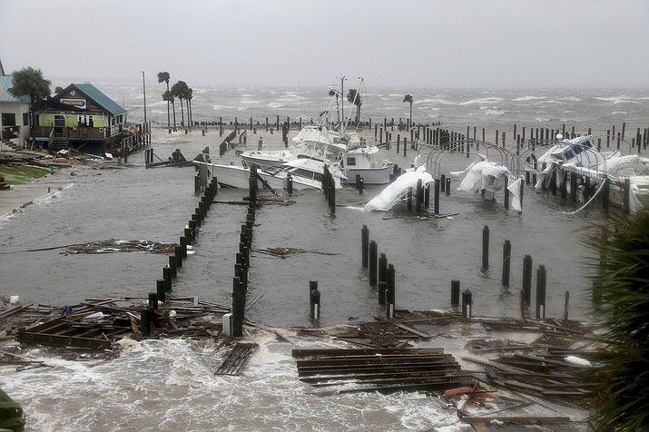Storm Surge retreats from inland areas, foreground, where boats lay sunk and damaged at the Port St. Joe Marina, Wednesday, Oct. 10, 2018 in Port St. Joe, Fla. (Douglas R. Clifford/Tampa Bay Times via AP)