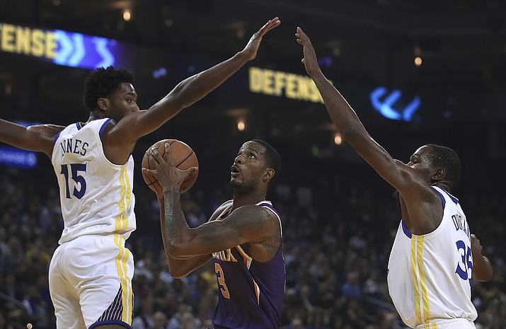 Phoenix Suns' Trevor Ariza, center, looks to shoot between Golden State Warriors' Damian Jones (15) and Kevin Durant, right, during the first half of a preseason NBA basketball game Monday, Oct. 8, 2018, in Oakland, Calif. (Ben Margot/AP)