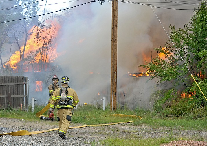 Central Yavapai and Prescott Fire Fighters work the scene of a structure fire near the intersection of Sheldon and Virginia Streets Saturday afternoon in Prescott. (Courier file photo)