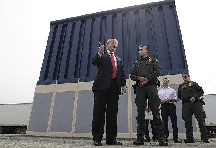 In this March 13, 2018, file photo, President Donald Trump speaks during as he reviews border wall prototypes, in San Diego, as Rodney Scott, the Border Patrol's San Diego sector chief, listens.  (AP Photo/Evan Vucci, File)