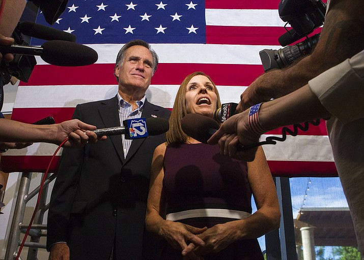 U.S. Rep. Martha McSally, R-Ariz., along with former Republican presidential nominee Mitt Romney, right, answers questions from the media during a Get Out the Vote Rally at the Gilbert Falls Event Center, Friday, Oct. 12, 2018, in Gilbert, Ariz. McSally will face U.S. Rep. Krysten Sinema, D-Ariz., in the November election as they seek the seat of retiring U.S. Sen. Jeff Flake, R-Ariz. (AP Photo/Darryl Webb)
