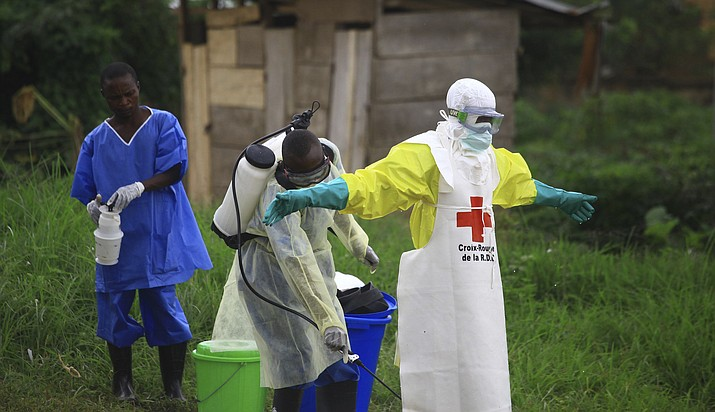In this Sept. 9 file photo, a health worker sprays disinfectant on his colleague after working at an Ebola treatment center in Beni, Eastern Congo. (Al-hadji Kudra Maliro/AP)