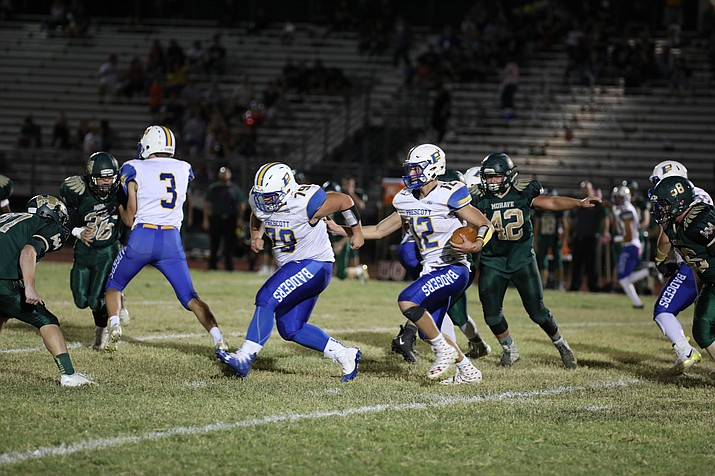 Prescott quarterback Austin Clark (12) follows his blockers and looks for a hole in the defense against Mohave on Friday, Oct. 12, 2018, in Bullhead City. Clark ran for three touchdowns in a 44-27 win over the Thunderbirds. (Jim Clark/Courtesy)