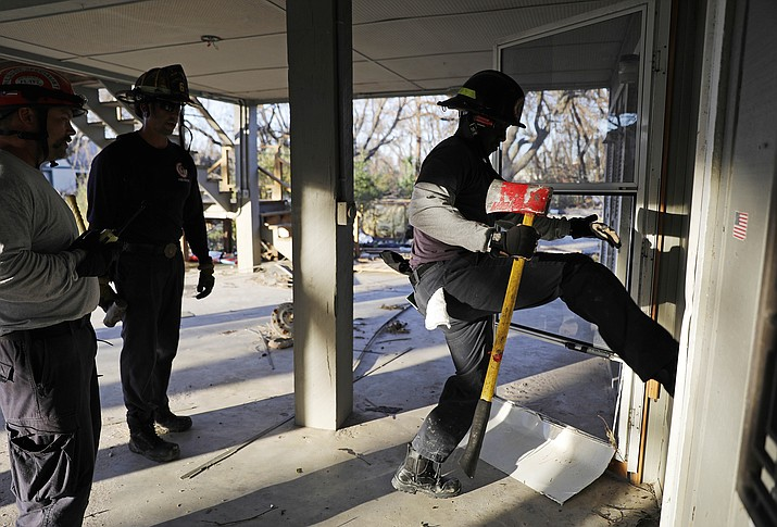 Members of a South Florida urban search and rescue team try to gain entry to a home while looking for survivors of hurricane Michael in Mexico Beach, Fla., Friday. (David Goldman/AP)