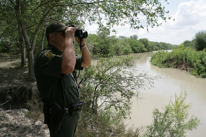 U.S. Border Patrol agent scans the area into Mexico with binoculars looking for illegal immigrants potentially staging to enter the United States. (Photo courtesy of U.S. Customs and Border Protection)