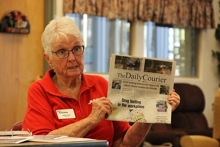 Sharon Gray, a local volunteer with AARP, uses a story published in a recent edition of The Daily Courier to caution attendees of an Arizona Fraud Watch presentation about the presence of con artists in the community. (Max Efrein/Courier)