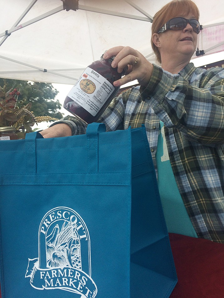 Pam Harris of Windswept Acres puts a jar of preserved beets into a reusable bag at the Prescott Farmers Market on Saturday, Oct 13. (Jason Wheeler/Courier)