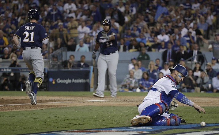 Los Angeles Dodgers catcher Yasmani Grandal goes after a passed ball as Milwaukee Brewers' Travis Shaw scores during the sixth inning of Game 3 Monday, Oct. 15, 2018, in Los Angeles. (Jae Hong/AP)