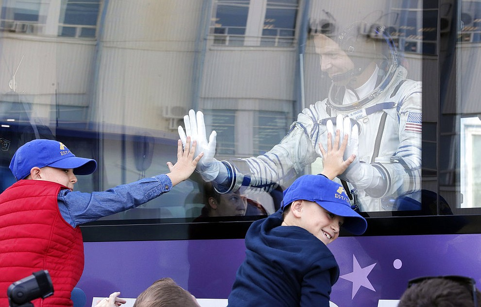 U.S. astronaut Nick Hague, member of the main crew to the International Space Station (ISS), waves to his sons from a bus prior to the launch of Soyuz-FG rocket at the Russian leased Baikonur cosmodrome, Kazakhstan, Thursday, Oct. 11, 2018. (AP Photo/Dmitri Lovetsky, Pool)
