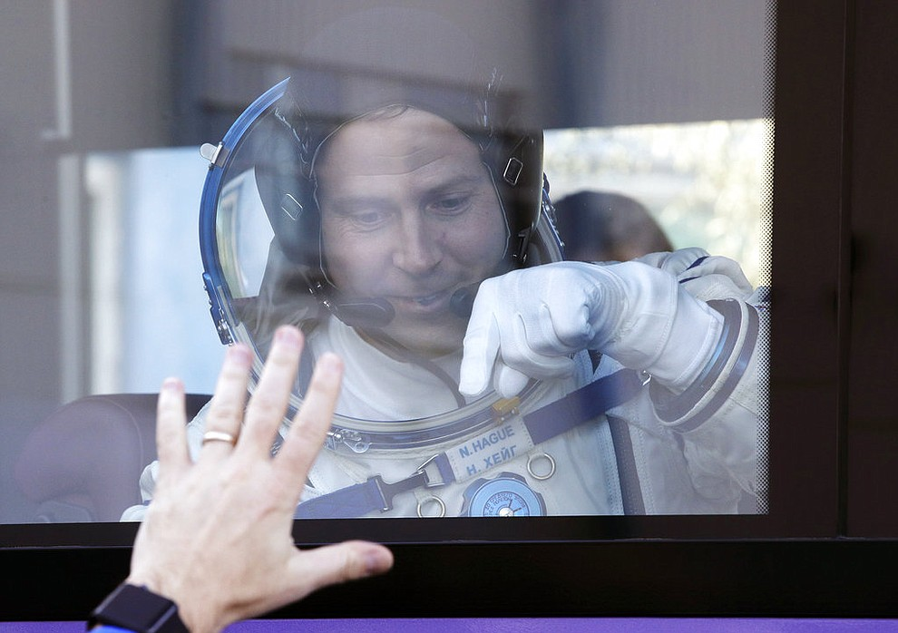 U.S. astronaut Nick Hague, member of the main crew to the International Space Station (ISS), waves to his relatives from a bus prior to the launch of Soyuz-FG rocket at the Russian leased Baikonur cosmodrome, Kazakhstan, Thursday, Oct. 11, 2018. (AP Photo/Dmitri Lovetsky, Pool)