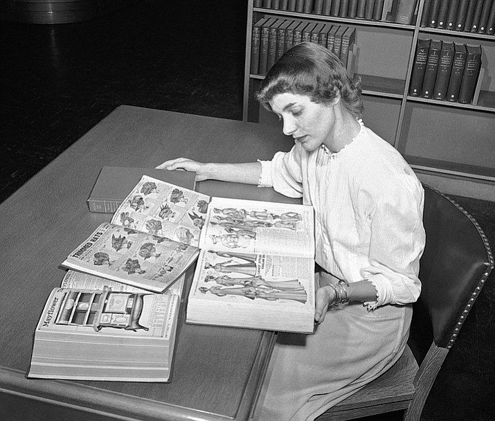 In an undated file photo, Ruth Parrington, librarian in the art department of the Chicago Public Library, studies early Sears Roebuck catalogs in the library's collection in Chicago. The catalog Parrington is holding features women's fashion from 1902. Sears has filed for Chapter 11 bankruptcy protection Monday, Oct. 15, 2018, buckling under its massive debt load and staggering losses. (AP Photo/File)
