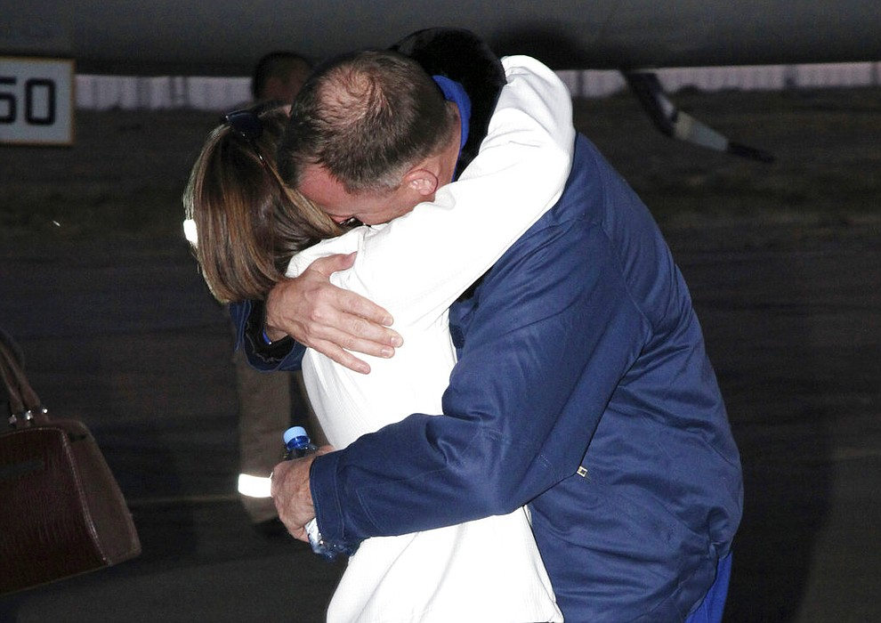 In this photo provided by Roscosmos, U.S. astronaut Nick Hague, right, embraces his wife Catie in Baikonur airport, Kazakhstan, Thursday, Oct. 11, 2018, after an emergency landing following the failure of a Russian booster rocket carrying them to the International Space Station. (Roscosmos via AP)