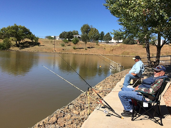 """Gary """"Papa Smurf"""" Knisley, right, and Roger Garcia relax in the sunshine Monday, Oct. 15, at Yavapai Lakes on Lakeshore Drive. Knisely said the two are considered the """"staple"""" fishermen of the lake, and they've had good luck with catching catfish. Garcia is a 57-year resident, and Knisley has lived in Prescott Valley for three years. (Sue Tone/Tribune)"""