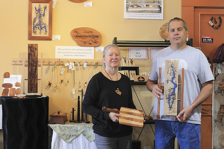 Sarah S. Loynd and Richard M. Kerrell display a cutting board and decorative art pieces at The Gallery in downtown Williams. Kerrell uses fractal wood burning on exotic wood to create unique pieces of art which are currently for sale. (Loretta Yerian/WGCN)