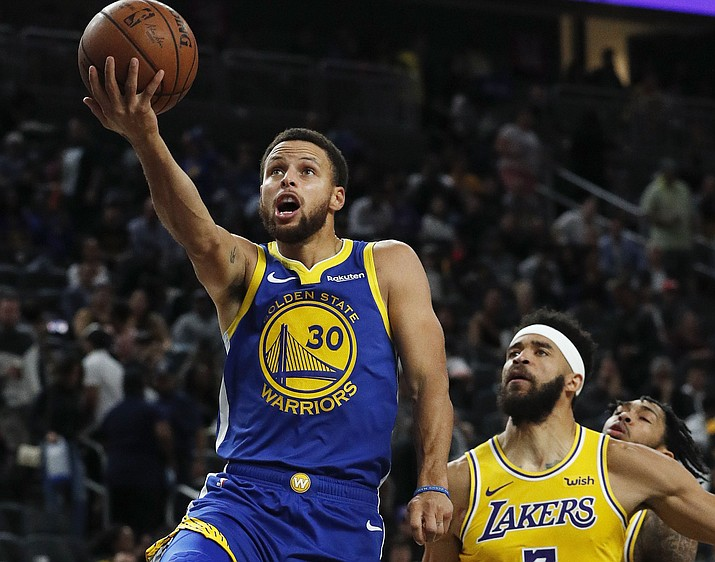 In this Oct. 10, 2018, file photo, Golden State Warriors guard Stephen Curry shoots next to Los Angeles Lakers center JaVale McGee during the second half a preseason basketball game in Las Vegas. (John Locher/AP, file)