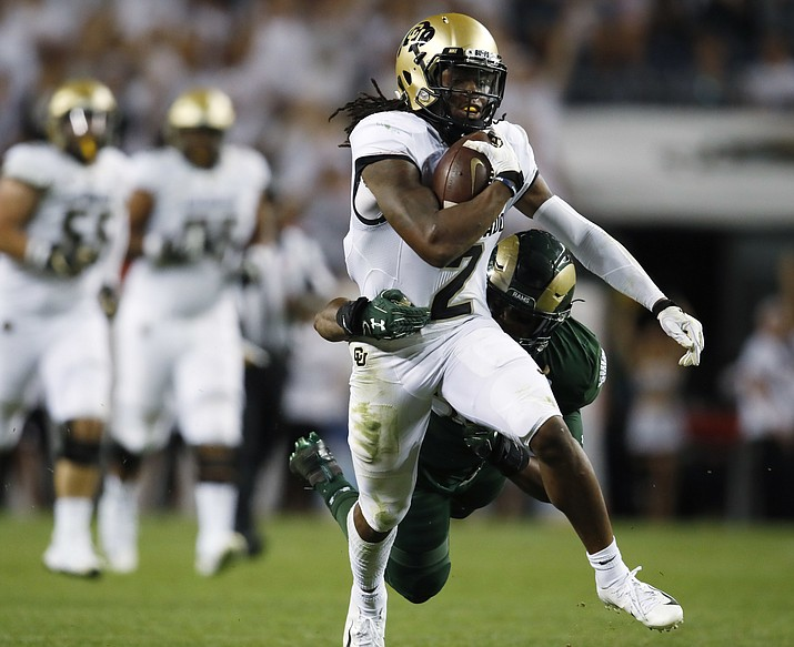 In this Aug. 31, 2018, file photo, Colorado wide receiver Laviska Shenault Jr., front, is pulled down after a long gain by Colorado State linebacker Josh Watson in the second half of an NCAA college football game, in Denver. Shenault was named to The Associated Press Midseason All-America team, Tuesday, Oct. 16, 2018. (David Zalubowski/AP, file)