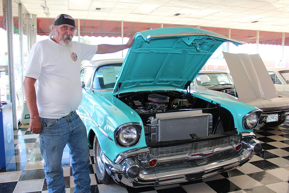 Jim Stephens, an employee at Dunton Motors Dream Machines, shows the turquoise 1957 Chevy he helped restore.
