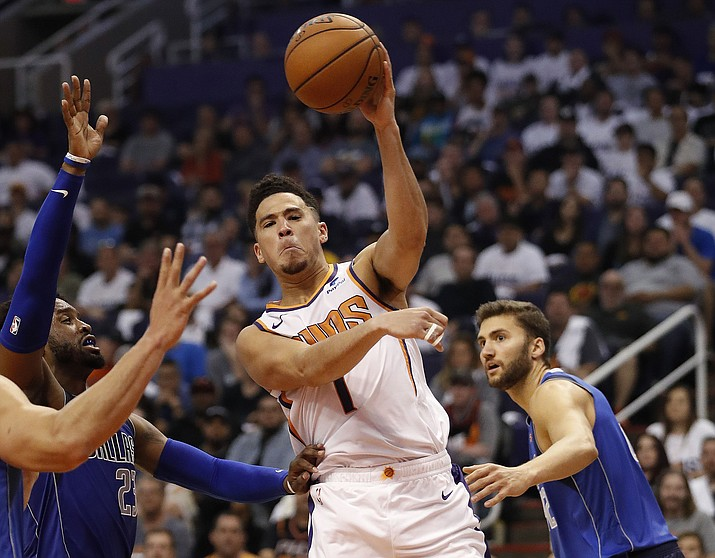 Phoenix Suns guard Devin Booker (1) passes around Dallas Mavericks guard Wesley Matthews (23) during the second half of an NBA basketball game Wednesday, Oct. 17, 2018, in Phoenix. Booker finished with 35 points in the Suns 121-100 win. (Matt York/AP)