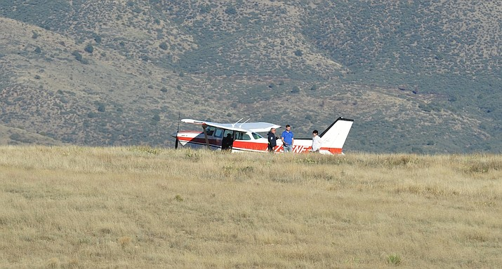 First-responders talk with a private airplane's two occupants east of Fain Road, after the pilot made an unscheduled landing there Friday afternoon, Oct. 19, 2018. (Les Stukenberg/Courier)