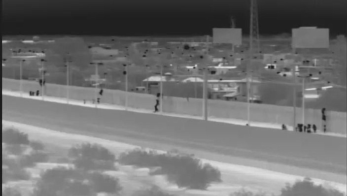 This image from video provided by the Yuma Sector Border Patrol shows a large group of Central American migrants being dropped over the U.S.-Mexico border wall east of the San Luis Port of Entry in Yuma, Arizona, on Friday, Oct. 19, 2018. (Yuma Sector Border Patrol)