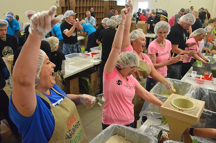 Members of the Sedona-Verde Valley Association of Realtors and the Layers Title group let out a cheer during the Manzanita Outreach food packing event Saturday in Cottonwood. VVN/Vyto Starinskas